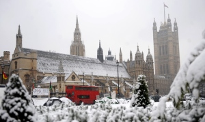 epa01987793 A London bus makes its way through a snowy Parliament Square in front of parliament in London, Britain 13 January 2010. Fresh snow has hit many parts of the UK, causing more problems for transport amid further limits on road gritting. Rail and air travellers face delays and cancellations, with several airports shut. Hundreds of schools are closed. Some pupils taking exams had difficult journeys on treacherous roads. Runways at Gatwick, London City and Birmingham International airports were closed because of snow, causing delays and cancellations.  EPA/ANDY RAIN