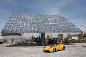This Amonix system consists of thousands of small lenses, each focusing sunlight to ~500X higher intensity onto a tiny, high-efficiency multi-junction solar cell.[1] A Tesla Roadster is parked beneath for scale.